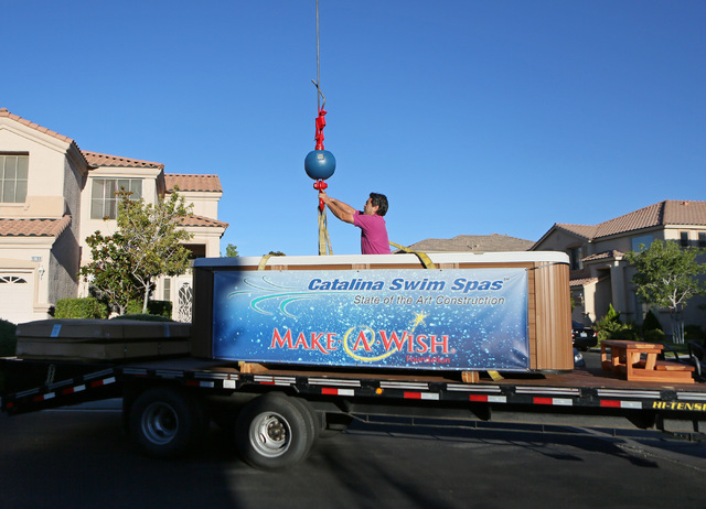 Steve Escarcega attaches a strap to a crane that will lift a 1,200-lb. swim spa into the air and over a two-story home into the Huebner's backyard as part of a Make-A-Wish reveal event Satu ...