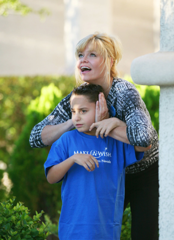 Cindy Huebner covers the ears of her son Vinnie as they watch a noisy crane in front of their house during a Make-A-Wish reveal event Saturday, Oct. 4, 2014, in Las Vegas. Make-A-Wish Southern Nev ...