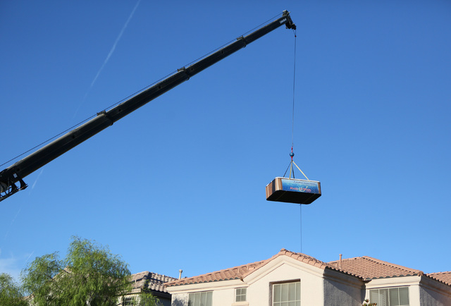 A 1,200-lb. swim spa is hoisted into the air and brought over a two-story home into the Huebner's backyard as part of a Make-A-Wish reveal event Saturday, Oct. 4, 2014, in Las Vegas. Make-A ...