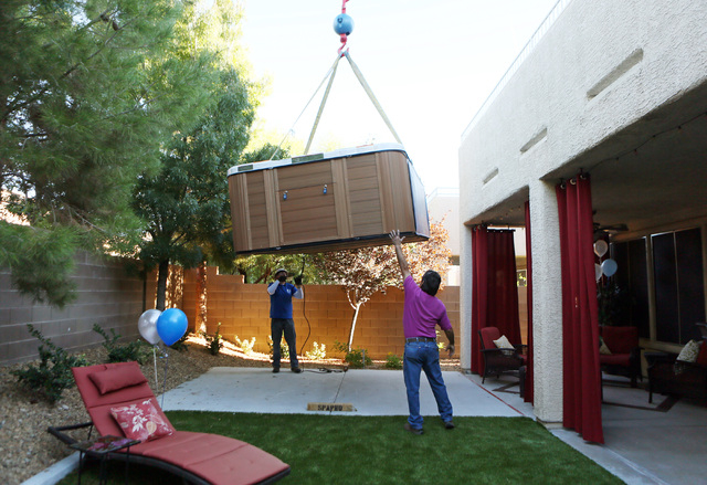 Nick Mattke, left, and Steve Escarcega work to steady a swim spa that is attached to a crane in the Huebner's backyard as part of a Make-A-Wish reveal event Saturday, Oct. 4, 2014, in Las Vegas. ...
