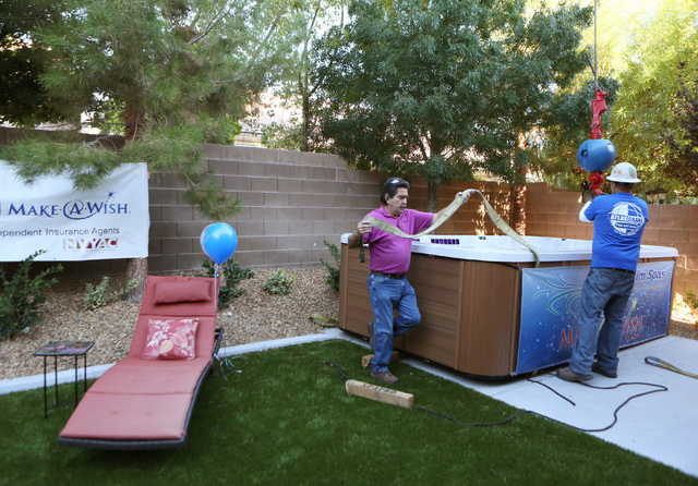 Steve Escarcega, center, and Nick Mattke work on a swim spa that was placed by a crane into the Huebner's backyard as part of a Make-A-Wish reveal event Saturday, Oct. 4, 2014, in Las Vegas ...