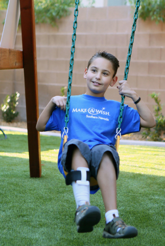 Vinnie Huebner, 9, left, smiles while swinging on his new playground during a Make-A-Wish reveal event Saturday, Oct. 4, 2014, in Las Vegas. Make-A-Wish Southern Nevada granted a wish for Vinnie,  ...