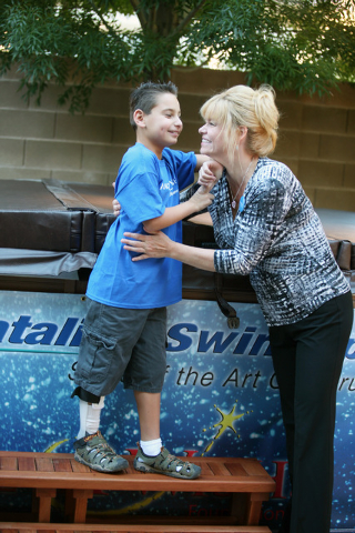 Vinnie Huebner, 9, left, and his mother Cindy share a moment during a Make-A-Wish reveal event Saturday, Oct. 4, 2014, in Las Vegas. Make-A-Wish Southern Nevada granted a wish for Vinnie, who surv ...