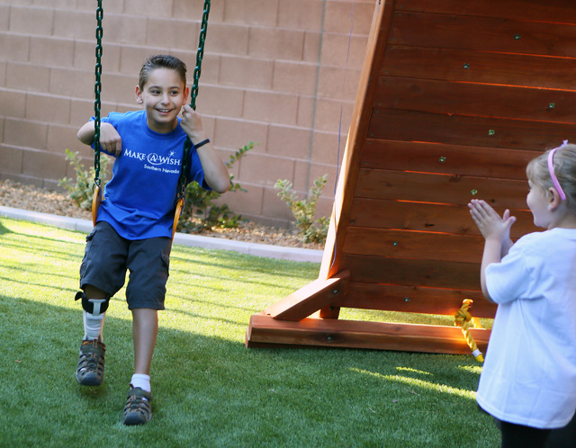 Vinnie Huebner, 9, left, looks to his sister Gianna, 5, who claps for him while Vinnie swings on his new playground during a Make-A-Wish reveal event Saturday, Oct. 4, 2014, in Las Vegas. His sist ...