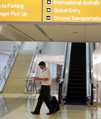 An unidentified pilot walks past beneath a sign at International terminal 3, on Friday, Oct. 10, 2014, at McCarran International Airport in Las Vegas.(Bizuayehu Tesfaye/Las Vegas Review-Journal)