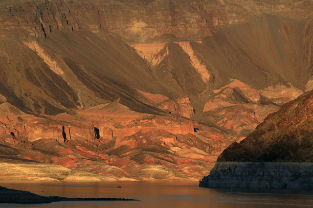 A boat plies the waters of Lake Mead as the setting sun lights up Painters Cove Monday, Oct. 6, 2014. (Sam Morris/Las Vegas Review-Journal)