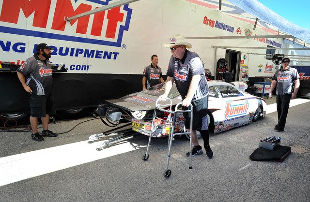 Team owner Ken Black, uses a walker to walk by his race cars before a pro stock qualifying session at the 14th annual NHRA Nationals at The Strip at the Las Vegas Motor Speedway on Friday, Oct. 31 ...