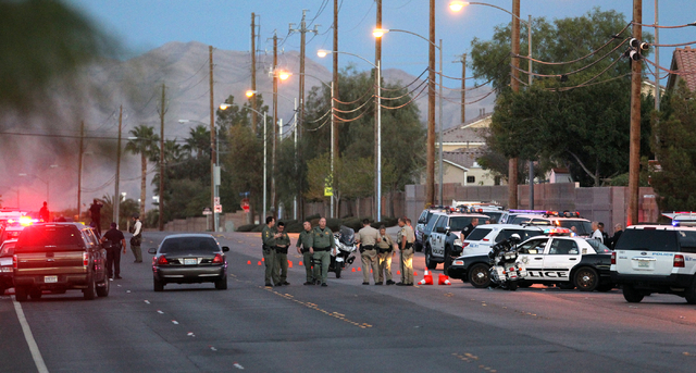 North Las Vegas and Las Vegas police blockade a neighborhood on West Alexander Road near North Martin Luther King Boulevard Wednesday, Oct. 8, 2014, where a suspect shot at an officer during an at ...