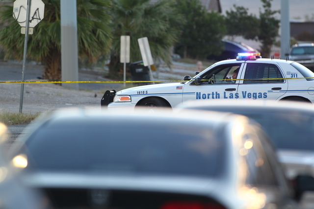 A North Las Vegas police officer sits at the intersection of Miller Avenue and Revere Street Wednesday morning, Oct. 8, 2014. A man was killed and an officer was wounded in a shootout Tuesday nigh ...