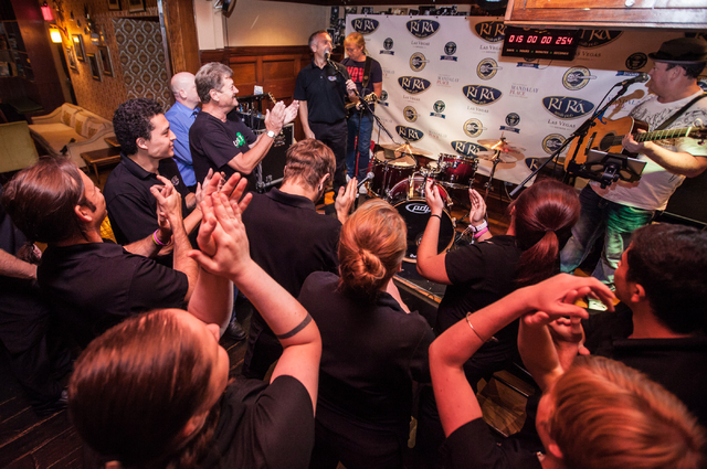 Restaurant staff and supporters cheer Dave Browne, upper center in back, and Dave Rooney, upper right, as Fergal Brady announces during a Guinness World Record attempt for Longest Concert by Multi ...