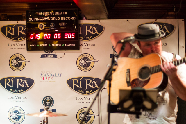 Dave Rooney prepares to perform with Dave Browne, not pictured, as the first act during a Guinness World Record attempt for Longest Concert by Multiple Artists at Ri Ra Irish Pub inside The Shoppe ...