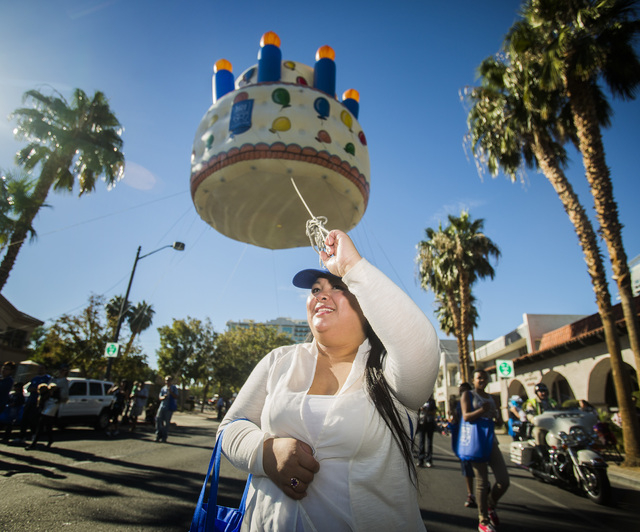 Anna Lynn holds an inflatable birthday cake during the   Nevada Day Parade on Fourth Street in downtown Las Vegas on Friday, Oct. 31. Thousands lined the street to celebrate Nevada's  Sesquicenten ...
