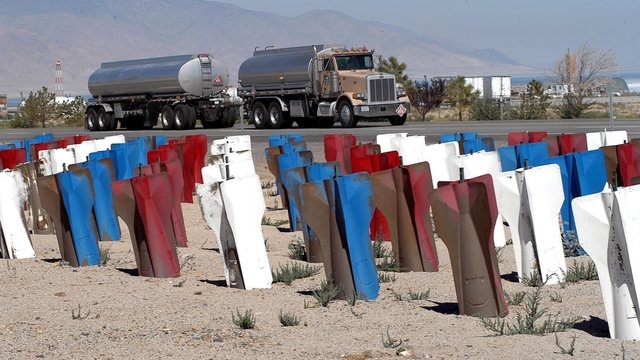 A semi passes a garden of bombs known as the Fin Field that greet visitors on the north side of Hawthorne, Nev. on Aug. 31, 2004.  A group of local residents have been turning the bombs from the H ...