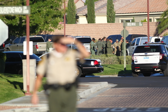 Las Vegas police gather outside of home in the 8500 block of Berkley Hall Street in northwest Las Vegas on Monday morning, Oct. 20, 2104, where there were reports of a domestic disturbance. (Chase ...