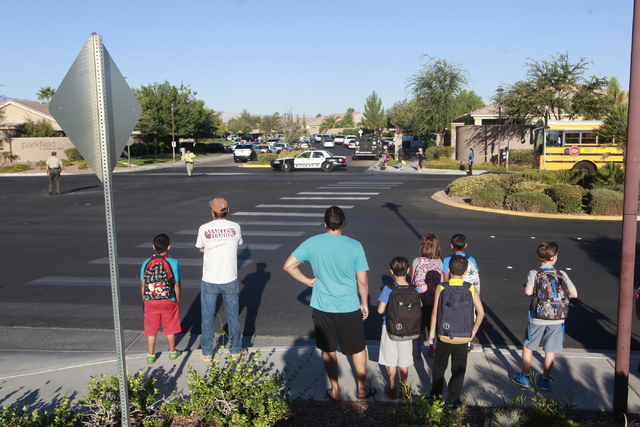 Children wait for a school bus as Las Vegas police and SWAT respond to a barricade situation at a home on the 8500 block of Berkley Hall Street in northwest Las Vegas on Monday morning, Oct. 20, 2 ...