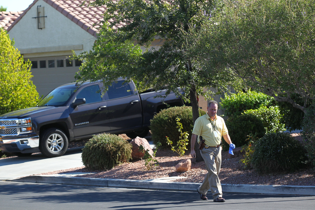 Las Vegas police investigate the scene where a woman was found dead and a man wounded in a home in the 8500 block of Berkley Hall Street in northwest Las Vegas on Monday, Oct. 20, 2014. (Chase Ste ...