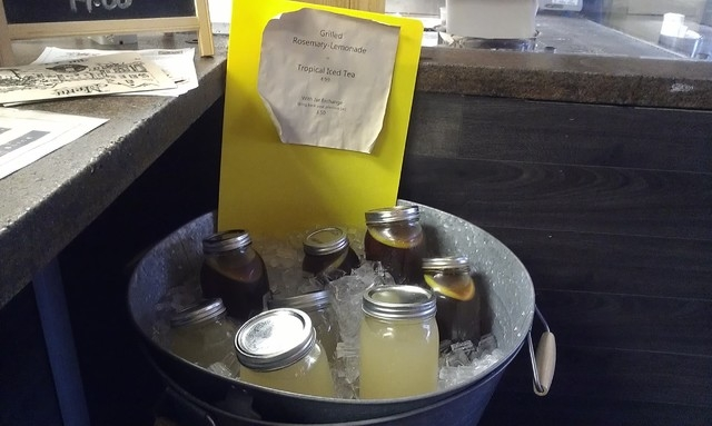 Jars of grilled-rosemary lemonade and tropical ice tea sit in ice at Old School Pizzeria. (Lisa Valentine/View)