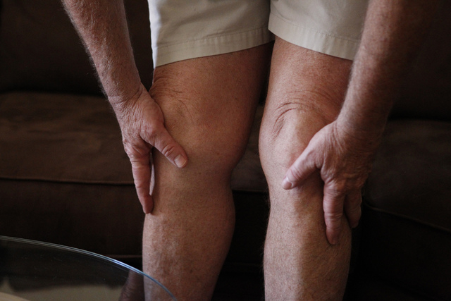 Brian Heilman holds his knees during an interview about his medical conditions at his home in Las Vegas Thursday, Oct. 9, 2014. Heilman's wife Diane uses hydrocodone, a drug to treat her rheumatoi ...