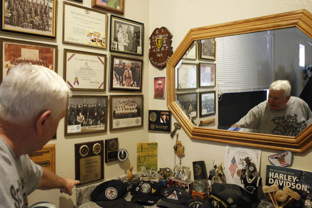 Brian Heilman shows pictures of his military and law enforcement career at his home in Las Vegas Thursday, Oct. 9, 2014. Heilman and his wife Diane take prescription drugs that have recently been  ...