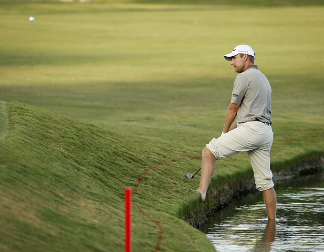 George McNeill hits the ball while standing in the water on the third playoff hole of the Justin Timberlake Shriners Hospitals for Children Open in Las Vegas Sunday, Oct. 18, 2009. McNeill lost th ...