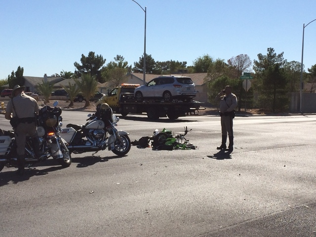 Las Vegas police officers investigate the collision of a scooter and a minivan Friday morning, Oct. 10, 2014, at Robindale Road and Spencer Street.(Bizu Tesfaye/Las Vegas Review-Journal)