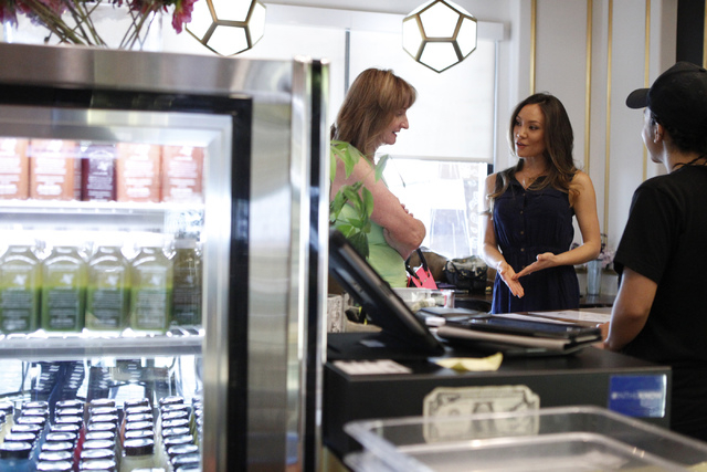 Jamie Stephenson, right, co-owner of The Juice Standard, explains their products to first time customer Jan Sanders at her shop in Las Vegas Saturday, Oct. 4, 2014. (Erik Verduzco/Las Vegas Review ...