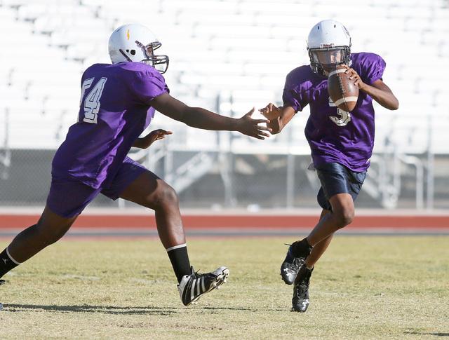 Sunrise Mountain senior quarterback Damon Heard, right, runs past Emmanuel Adeyemi during a practice at Sunrise Mountain High School Wednesday, Oct. 15, 2014, in Las Vegas. Sunrise Mountain won th ...