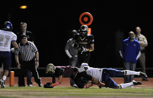 Faith Lutheran Crusaders wide receiver Mark Rubalcaba scores a touchdown despite being tackled by Sierra Vista safety Randall Grimes (12) in the first half of their high school football game at Fa ...