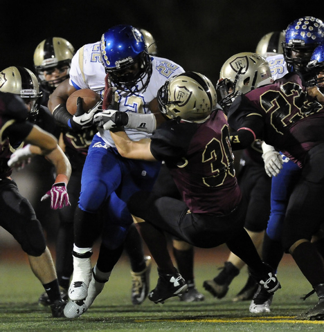Faith Lutheran Crusaders linebacker Cole Thomas (30) tackles Sierra Vista running back Randall Grimes (12) in the first half of their high school football game at Faith Lutheran High School in Las ...