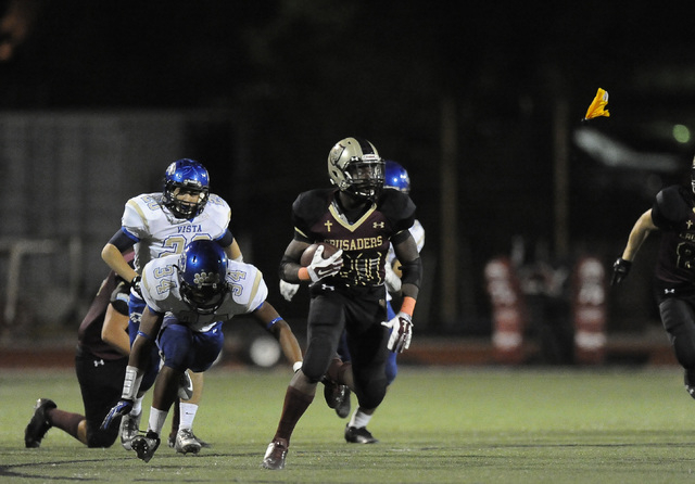 Faith Lutheran running back Alfred Soboyejo IV (20) breaks the tackle of Sierra Vista linebacker  Christopher Byrd (34) as a penalty marker flies in the background to gain a first down in the seco ...