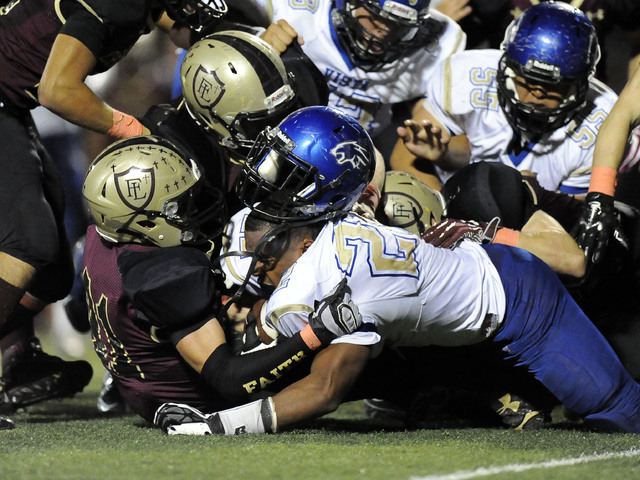 The helmet worn by Sierra Vista running back Daniel Godfrey (22) flies off while being tackled by Faith Lutheran linebacker Tyler Mahan in the second half of their high school football game at Fai ...