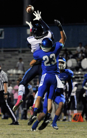 Canyon Springs' Kujuan Casey, grabs a reception against Green Valley's Albert Lake during a high school football game at Green Valley High School on Friday, Oct. 17, 2014. (David Becker/Las Vegas  ...