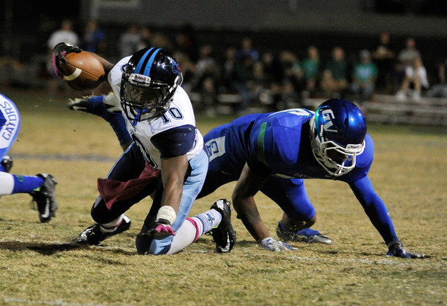 Canyon Springs' Jerrod Blackwell (10) reaches for extra yardage against Green Valley's David Otuafi during a high school football game at Green Valley High School on Friday, Oct. 17, 2014. (David  ...