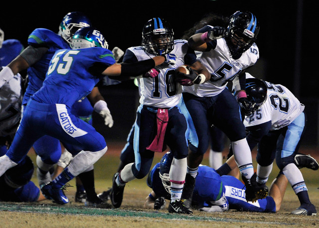 Canyon Springs' Jerrod Blackwell (10) finds a hole as he runs with the ball against Green Valley during a high school football game at Green Valley High School on Friday, Oct. 17, 2014. (David Bec ...
