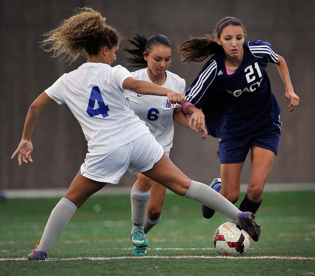 Legacy High School's Nadia Hernandez (21) is double teamed by Bishop Gorman's Addison Birotte (4) and Jordan Karsting during a soccer match at Bishop Gorman High School on Tuesday, Oct. 7, 2014. H ...