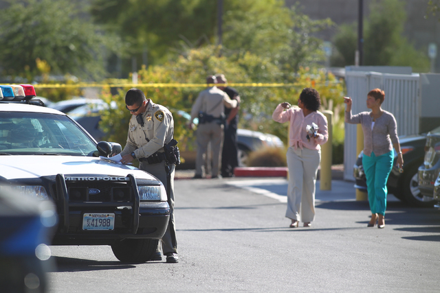 Las Vegas police respond to the scene of a shooting at a business complex as employees walk through the parking lot at 2200 S. Rancho Dr. in Las Vegas on Monday, Oct. 13, 2014. The person who was  ...