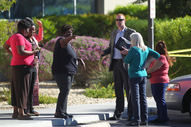 A Las Vegas police detective, center right, talks with employees of a business complex as police respond to the scene of a shooting at 2200 S. Rancho Dr. in Las Vegas on Monday, Oct. 13, 2014. The ...