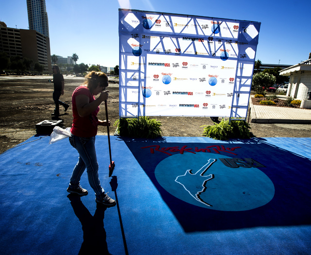 Babriela Montes sweeps the carpet during the Rock in Rio USA Rock Street sneak-peek event at the site of the former Circus Circus RV Park on Monday, Oct. 27, 2014. The permanent open-air concert v ...