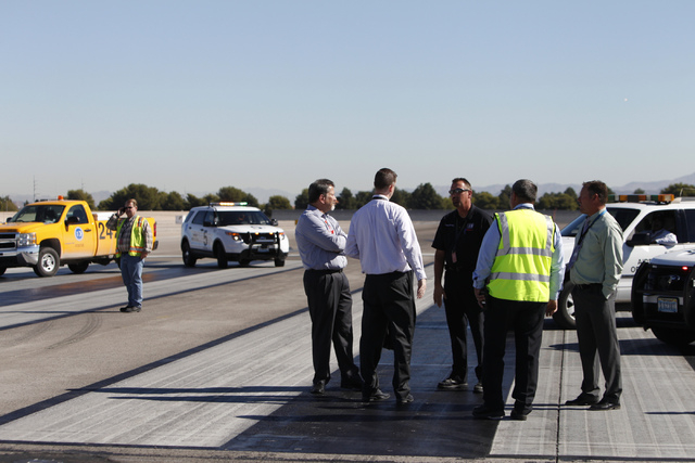 Airport officials stand on the east west runway at McCarran International Airport in Las Vegas is seen on Wednesday, Oct. 29, 2014. The east west runway at the airport begun the first phase of a $ ...
