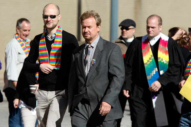 Rev. Frank Schaefer, center, and his son, Tim Schaefer, second from left, walk to a meeting of the Judicial Council of the United Methodist Church, in Memphis, Tenn., Wednesday, Oct. 22, 2014. The ...