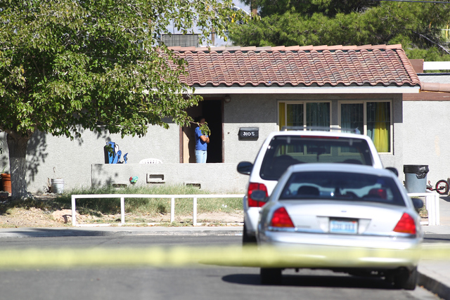 An area resident watches as Las Vegas police respond to a barricade situation involving an armed robbery suspect inside of a home by Ronnow Elementary School, near Washington Avenue and Pecos Road ...