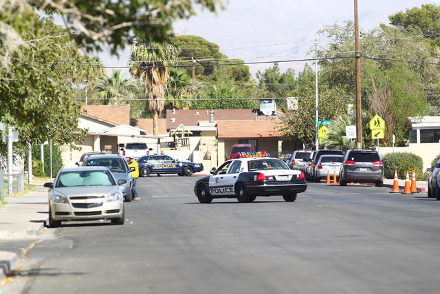 Las Vegas police make their way to a barricade situation involving an armed robbery suspect inside of a home by Ronnow Elementary School, near Washington Avenue and Pecos Road, in Las Vegas on Wed ...