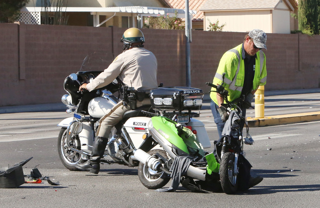 A worker from Quality Towing removes a damaged scooter from an accident scene on Friday, Oct. 10, 2014, at the corner of Spencer Road and Robindale Street in Las Vegas. A 20-year-old man on the sc ...