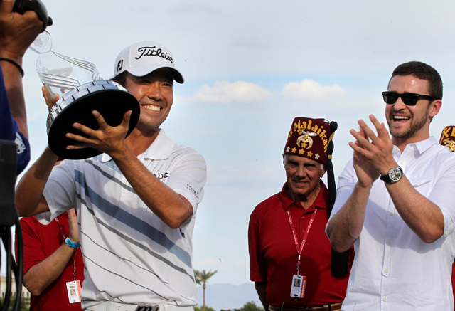 Kevin Na hold the glass trophy while Justin Limberlake applauds during the  the annual Justin Timberlake Shriners Hospitals for Children Open at TPC Summerlin golf club in Las Vegas on Sunday , Oc ...