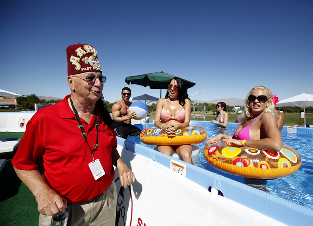 Brittani Medina, center, and Joyce Jones, right,speak with Sandy Kahn, left, a Shriner from San Ramon, Calif., at the pool perched above the 18th fairway at TPC Summerlin during the final round of ...