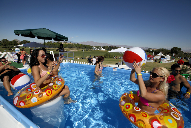 Brittani Medina, left, and Joyce Jones, right, lounge in a pool perched above the 18th fairway at TPC Summerlin during the final round of the Shriners Hospital for Children Open in Las Vegas on Su ...