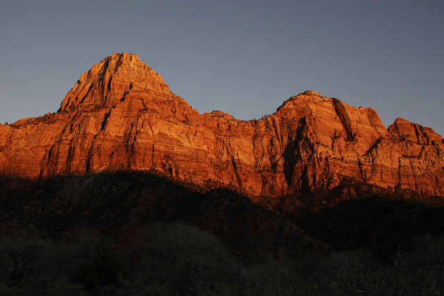 Shadows creep up the sandstone cliffs as the sun sets on Utah's Zion National Park. A 47-year-old California man rock-climbing in Utah's Zion National Park died over the weekend after falling in ...