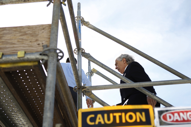 U.S. Department of Energy Secretary Ernest Moniz walks to a solar panel installment project on the roof of Mandalay Bay Convention Center in Las Vegas during a tour Wednesday, Oct. 22, 2014. The s ...