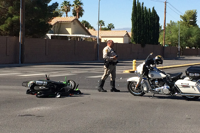 A Las Vegas police officer stands near a scooter that was involved in an accident Friday morning, Oct. 10, 2014, at Robindale Road and Spencer Street. (Bizu Tesfaye/Las Vegas Review-Journal)