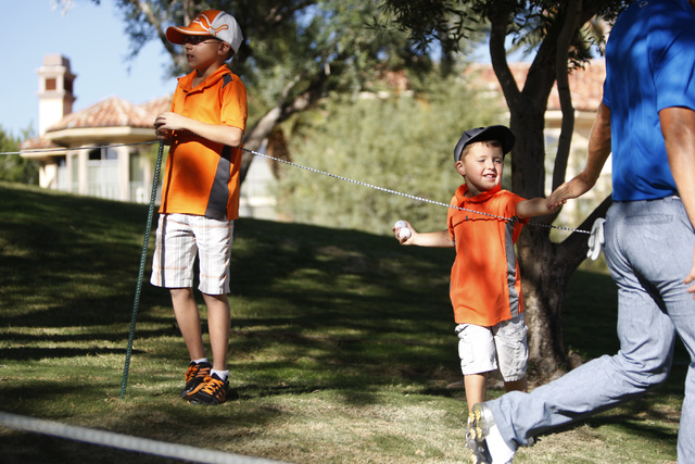 Jack Nelson, right, 4, high fives professional golfer Derek Ernst, with his brother Cooper, 9, at the Shriners Hospitals for Children Open golf tournament at TPC Summerlin, 1700 Village Center Cir ...